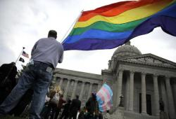 """Gay-rights supporter Mathew """"Skippy"""" Mauldin holds a flag during a gay rights rally outside the Capitol in Jefferson City, Mo."""