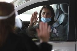 In this Friday, June 26, 2020 photo, U.S. District Judge Laurie Michelson, left, administers the Aath of Citizenship to Hala Baqtar during a drive-thru naturalization service in a parking structure at the U.S. Citizenship and Immigration Services headquarters on Detroit's east side