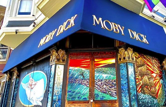 Moby Dick Bar, with recent murals painted on its boarded doors and windows
