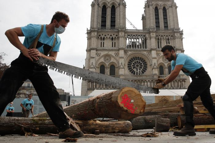 Carpenters put the skills of their Medieval colleagues on show on the plaza in front of Notre Dame Cathedral in Paris, France, Saturday, Sept. 19, 2020.