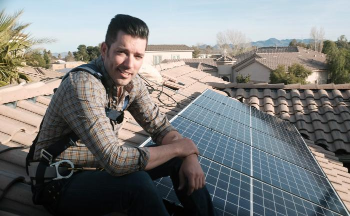 "This image released by Independent Lens shows Jonathan Scott from ""Property Brothers"" installing solar panels on a rooftop in his new documentary ""Jonathan Scott's Power Trip."""