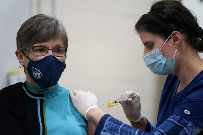 Public health nurse Lisa Horn gives a COVID-19 vaccine injection to Kansas Democratic Gov. Laura Kelly.