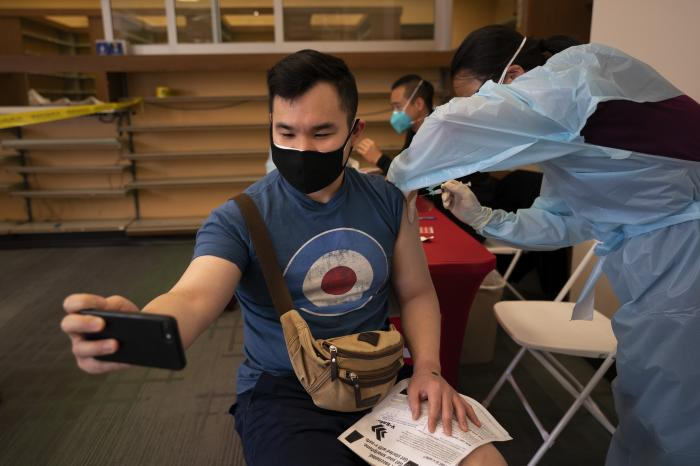 Freeson Wong, 31, takes a selfie as he receives a dose of the Moderna vaccine at a vaccination center in the Chinatown neighborhood of Los Angeles.