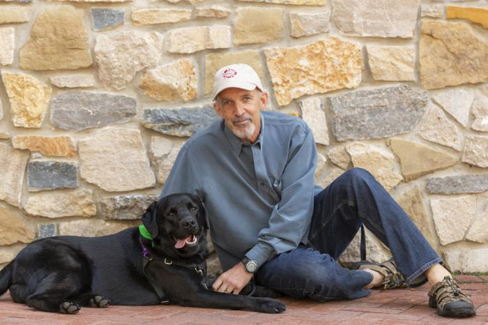Philip Tedeschi, director emeritus of the Institute for Human-Animal Connection at the University of Denver, poses with his dog, Samara, on campus in Denver on July 25, 2018