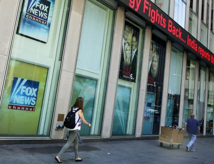 People pass the News Corporation headquarters building and Fox News studios in New York on Aug. 1, 2017.