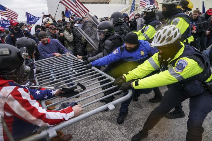 In this Jan. 6, 2021, file photo violent insurrectionists loyal to President Donald Trump hold on to a police barrier at the Capitol in Washington
