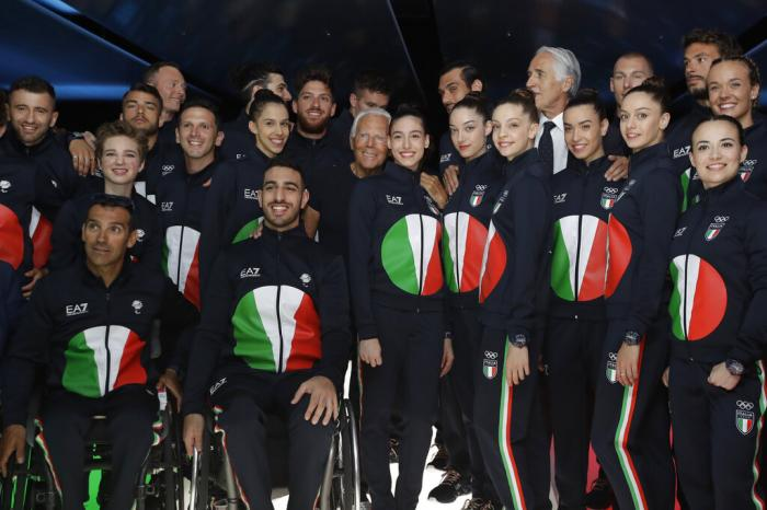Designer Giorgio Armani, centre, poses with Italian Olympic athletes at the end of the Emporio Armani men's Spring-Summer 2020 collection.