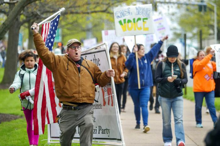 Opponents of a bill to repeal Connecticut's religious exemption for required school vaccinations march down Capitol Avenue before the State Senate voted on legislation, in Hartford, Conn.